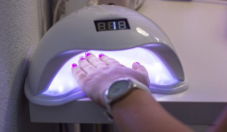 Professional manicure in salon. White uv lamp. Close up concept. Beauty background. Hands polish manicure nails. Ultraviolet equipment.